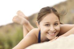 Mujer sonriente del Latino que se acuesta en la playa Fotos de archivo