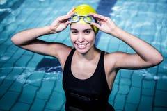 Mujer sonriente del nadador que sostiene sus vidrios que nadan Imagen de archivo libre de regalías