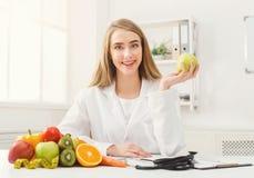 Mujer sonriente del nutricionista con la manzana en la oficina fotografía de archivo