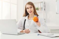 Mujer sonriente del nutricionista con la naranja en la oficina imagen de archivo