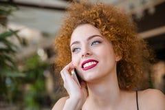 Mujer sonriente del pelirrojo que habla en el teléfono Imagen de archivo libre de regalías