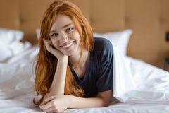 Mujer sonriente del pelirrojo que miente en la cama Fotografía de archivo