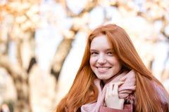 Mujer sonriente del pelirrojo que mira la cámara al aire libre Fotografía de archivo libre de regalías