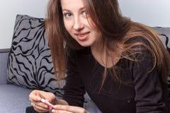 Mujer sonriente del resultado positivo de la prueba de embarazo Fotos de archivo