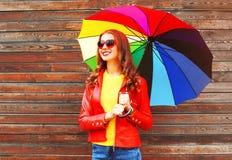 Mujer sonriente del retrato con el paraguas colorido en otoño Imagen de archivo libre de regalías