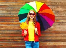 Mujer sonriente del retrato con el paraguas colorido en otoño con las hojas de arce Foto de archivo