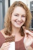 Mujer sonriente del tamaño extra grande que come la barra del chocolate Foto de archivo