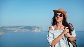 Mujer sonriente del viaje en sombrero y gafas de sol que camina encima de la montaña sobre tiro medio del mar almacen de metraje de vídeo