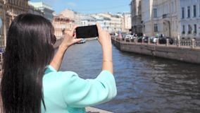 Mujer sonriente del viaje que goza tirando el vídeo del canal y del paisaje urbano del agua del terraplén en ciudad europea almacen de metraje de vídeo