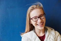 Mujer sonriente delante de una pared azul Imagen de archivo