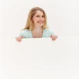 Mujer sonriente detrás de la tarjeta blanca en blanco Imagen de archivo libre de regalías