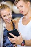 Mujer sonriente e instructor personal con la tableta en el gimnasio de la aptitud Foto de archivo