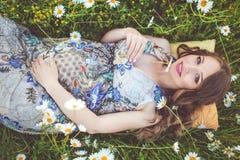 Mujer sonriente embarazada hermosa que miente en el campo de la manzanilla Fotografía de archivo libre de regalías