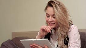 Mujer sonriente emocionada que tiene llamada video en la tableta mientras que se sienta en su cama metrajes