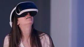 Mujer sonriente en auriculares de la realidad virtual que disfruta de su experiencia Foto de archivo libre de regalías