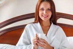 Mujer sonriente en café de consumición del dormitorio en cama Imagen de archivo libre de regalías