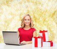 Mujer sonriente en camisa roja con los regalos y el ordenador portátil Foto de archivo