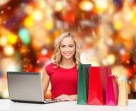 Mujer sonriente en camisa roja con los regalos y el ordenador portátil Imagen de archivo libre de regalías