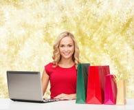 Mujer sonriente en camisa roja con los regalos y el ordenador portátil Imagen de archivo