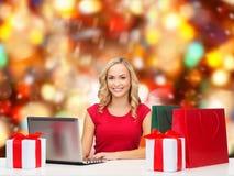 Mujer sonriente en camisa roja con los regalos y el ordenador portátil Foto de archivo libre de regalías