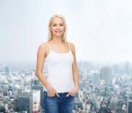 Mujer sonriente en camiseta blanca en blanco Foto de archivo libre de regalías