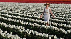 Mujer sonriente en campos del tulipán Fotos de archivo