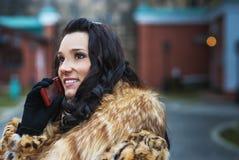 Mujer sonriente en capa marrón con el teléfono imagenes de archivo
