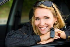 Mujer sonriente en coche con claves Imágenes de archivo libres de regalías