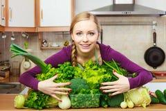Mujer sonriente en cocina con las verduras verdes Fotografía de archivo