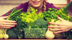 Mujer sonriente en cocina con las verduras verdes Imagenes de archivo
