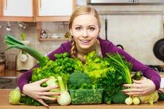 Mujer sonriente en cocina con las verduras verdes Fotos de archivo