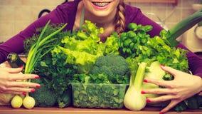 Mujer sonriente en cocina con las verduras verdes Fotos de archivo libres de regalías