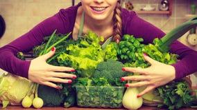 Mujer sonriente en cocina con las verduras verdes Imagen de archivo libre de regalías