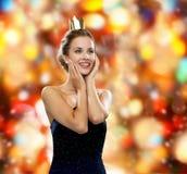 Mujer sonriente en corona que lleva del vestido de noche Foto de archivo