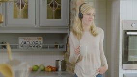 Mujer sonriente en el baile de consumición del café de la cocina y el escuchar la música en sus auriculares almacen de video