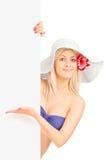 Mujer sonriente en el bikini que se coloca y que gesticula en un panel Imágenes de archivo libres de regalías