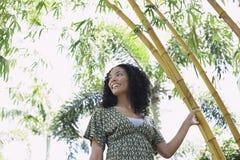 Mujer sonriente en el bosque de bambú Foto de archivo libre de regalías