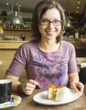 Mujer sonriente en el café que come el postre de la tarta de manzanas con crema Imagenes de archivo