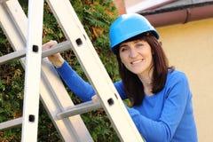 Mujer sonriente en el casco azul que sube en la escalera de aluminio Imagen de archivo