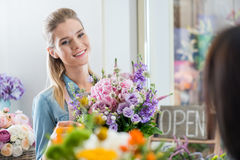 Mujer sonriente en el delantal que sostiene el ramo y que mira lejos en floristería fotografía de archivo libre de regalías