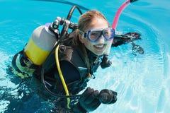 Mujer sonriente en el entrenamiento del equipo de submarinismo en piscina Foto de archivo libre de regalías