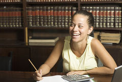 Mujer sonriente en el escritorio Fotografía de archivo libre de regalías