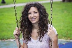 Mujer sonriente en el oscilación del parque Fotografía de archivo libre de regalías