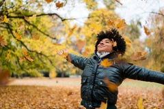 Mujer sonriente en el parque, brazos extendidos Imagenes de archivo