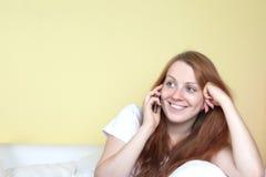 Mujer sonriente en el sofá que habla en el teléfono Imágenes de archivo libres de regalías