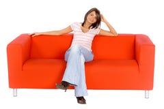 Mujer sonriente en el sofá anaranjado Imagen de archivo libre de regalías