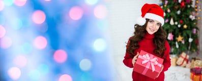 Mujer sonriente en el sombrero de santa con la caja de regalo La Navidad Imagen de archivo libre de regalías