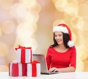 Mujer sonriente en el sombrero de santa con los regalos y el ordenador portátil Imágenes de archivo libres de regalías