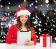 Mujer sonriente en el sombrero de santa con PC del regalo y de la tableta Imagenes de archivo