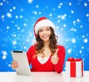 Mujer sonriente en el sombrero de santa con PC del regalo y de la tableta Foto de archivo libre de regalías